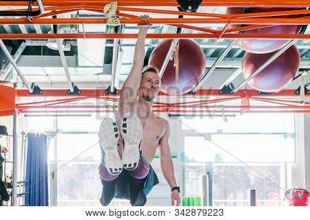 Strong shirtless male athlete shows calisthenic moves Hanging on pull bar one arm leg raises or l-sit hold stock photo