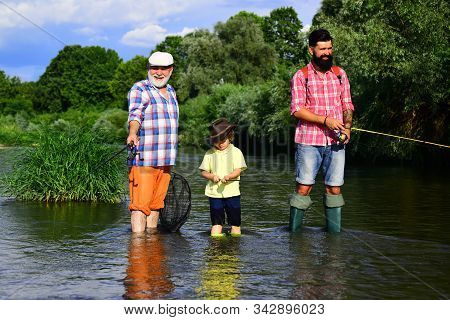 Grandfather, father and grandson fishing together. Grandson with father and grandfather fishing by lake. Father, son and grandfather fishing stock photo