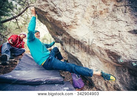 Athletic man climbing hard boulder problem in forest. Sport climbing, bouldering. Outdoor. Top view of gripping hand. stock photo
