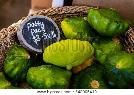 A close up view of a wicker basket filled with patty pans, a variety of summer squash, and price sign on a market stall during an agricultural fair stock photo