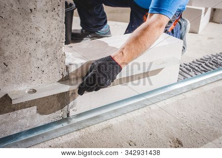 The master monitors the wall with gas blocks using glue and trowel stock photo