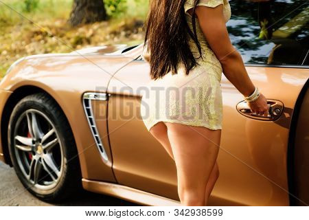 Sexy young hot woman with slim body wearing mini dress and posing near her car. Attractive female in short dress and long brunette hair opening door of her expensive golden car stock photo