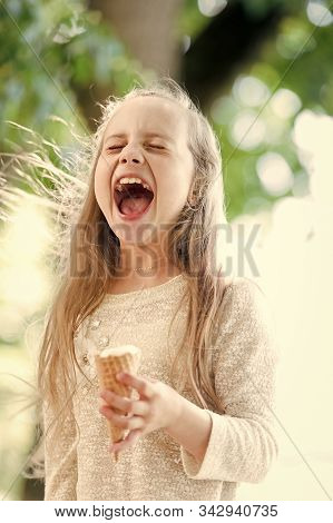 Ice cream makes her fall into euphoria. Cute little girl eating ice cream on summer day. Small child licking ice cream in cone outdoor. Adorable happy kid enjoying frozen iced cream dessert. stock photo