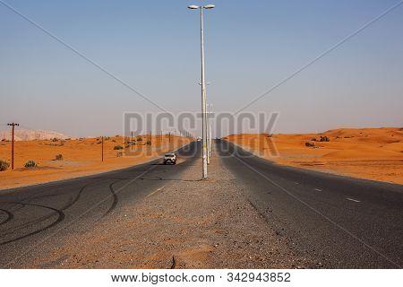 Winding black asphalt road through sand dunes, United Arab Emirates stock photo