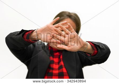 Woman holding her hand stretched out toward the camera, covering her face, avoiding to be seen or stopping a problems. Woman hide her face at hand isolated on white background. stock photo