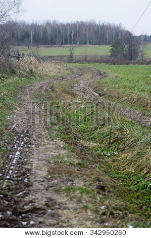 Rural road in a field with dry grass. Old rural road in a field with dry gray grass stock photo