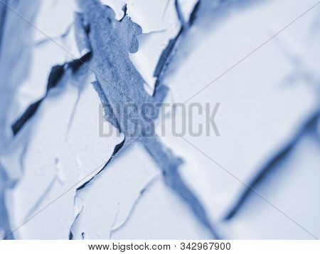 Light blue painted old exterior wall closeup with cracked, scratched and peeling paint, abstract abandoned backdrop, blue flaking paint texture stock photo