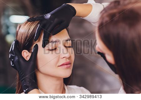 beautician- makeup artist applies paint henna on previously plucked, design, trimmed eyebrows in a beauty salon in the session correction. Professional care for face. stock photo