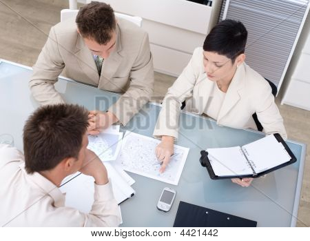 Businessteam of three working together sitting around a desk high angle view. stock photo