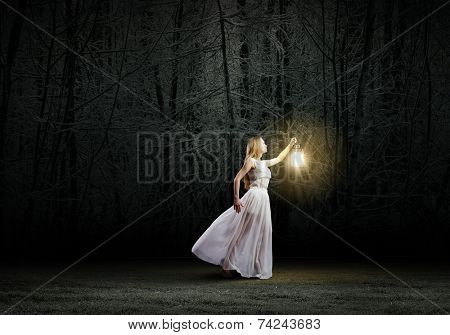 Young woman with lantern walking in dark forest stock photo