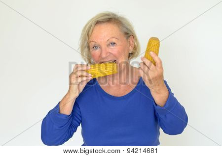 Elderly lady enjoying fresh corn on the cob biting into the kernels with a happy smile in a healthy diet concept over grey stock photo