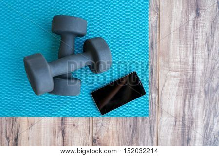 Fitness at home: free weights, yoga mat, mobile phone app. Dumbbells on blue exercise mat and smartp
