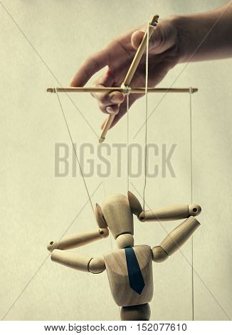 Puppet on a string in the hands of puppeteer. Doll holding on to the head portraying panic. Puppet is presented in business style with a tie. stock photo