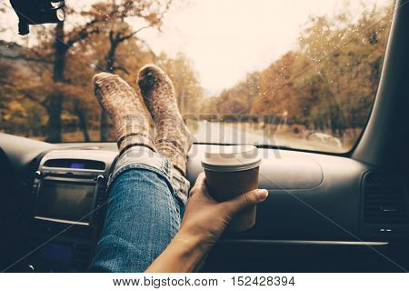 Woman feet in warm socks on car dashboard. Drinking take away coffee on road. Fall trip. Rain drops