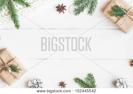 Christmas composition. Christmas gift knitted blanket pine cones fir branches. Flat lay top view