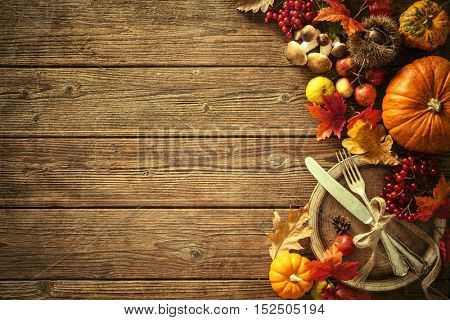 Autumn background from fallen leaves and fruits with vintage place setting on old wooden table. Than