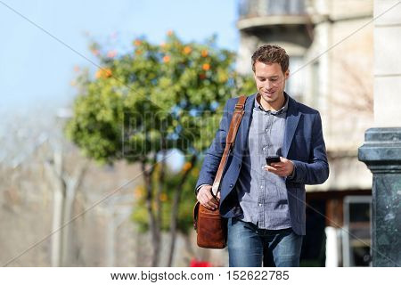 Young urban businessman professional on smartphone walking in street using mobile phone app texting
