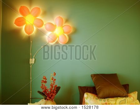 Fun pink flower lights against green feature wall in child's bedroom. stock photo
