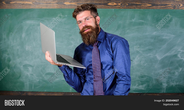 adult,back,background,beard,bearded,blackboard,call,caucasian,chalkboard,computer,concept,conferencing,director,distance,education,examiner,eyeglasses,formal,handsome,headteacher,hipster,hold,intelligent,internet,laptop,learn,lesson,male,man,mature,modern,moustache,mustache,necktie,notebook,professor,school,smart,smile,study,surfing,teach,teacher,to,unshaven,video,wear