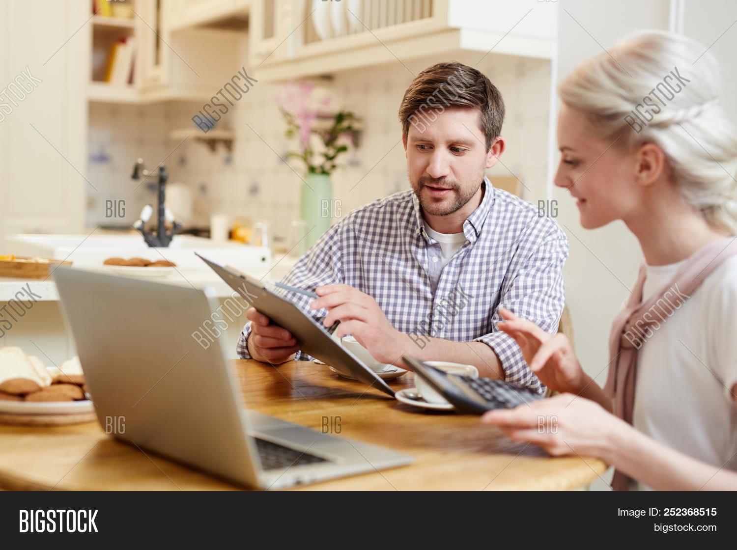 accounting,adult,banking,bill,budget,calculating,communication,computer,content,couple,discussing,domestic,examining,explaining,family,finance,home,kitchen,laptop,looking,man,paper,people,saving,showing,talking,tax,technology,woman,young