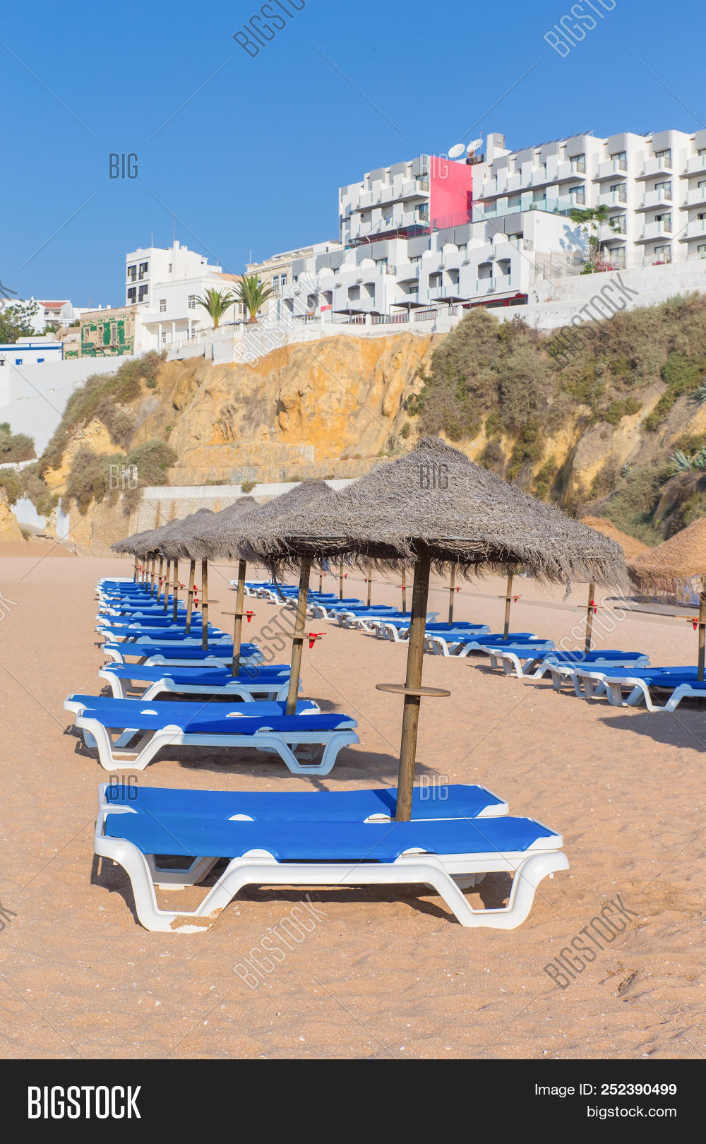 Rows Of Sunbeds With Parasols On Portuguese Beach In