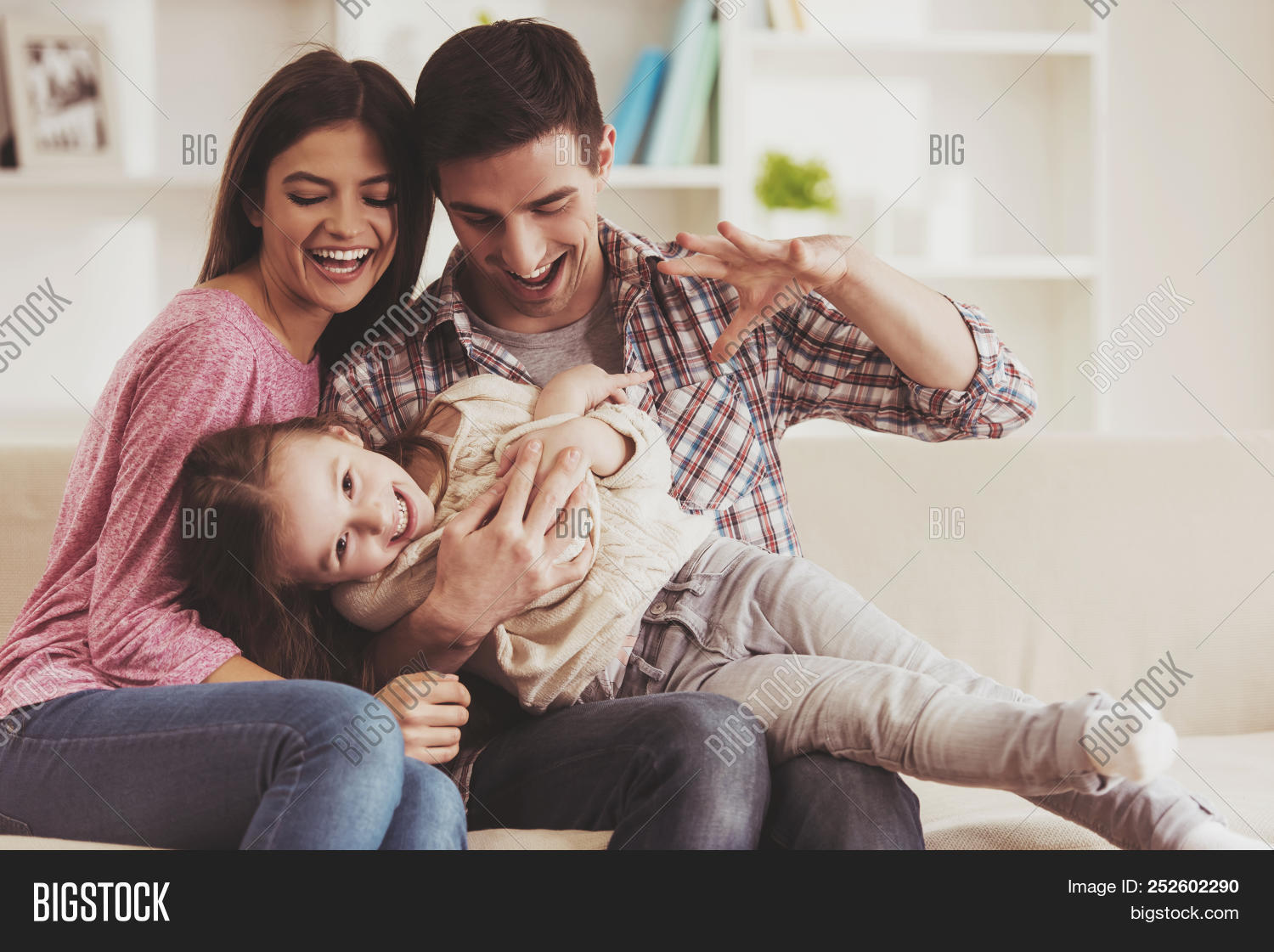 atrractive,child,childhood,concept,couple,daughter,family,father,female,flat,fun,funny,future,girl,hands,happiness,happy,house,hugging,huggs,indoors,interior,joy,joyful,kid,laing,leisure,lifestyle,little,living,love,lover,man,merried,mother,parents,people,playing,portrait,room,sitting,smile,sofa,together,woman,young