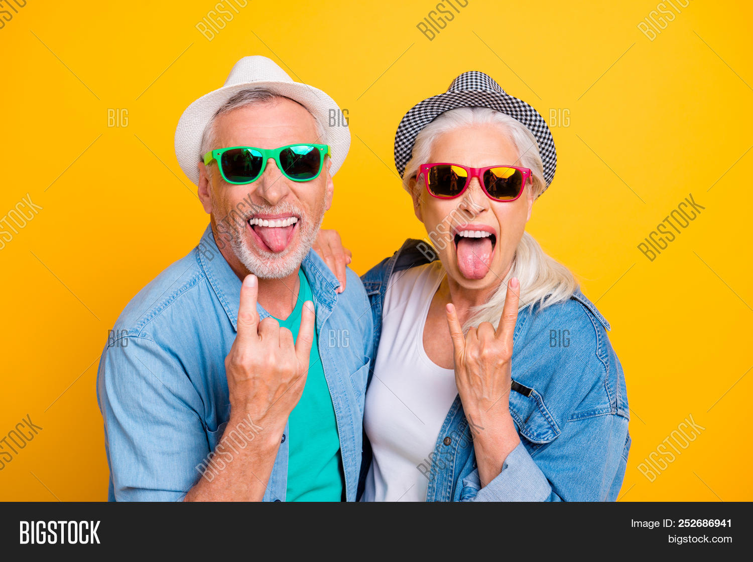 adult,age,couple,crazy,elderly,eyeglasses,eyewear,family,fan,female,fingers,friends,fun,gesture,glasses,grandfather,grandmother,gray-haired,grimacing,happy,hat,headwear,horned,husband,jeans,joy,love,lovers,mad,male,man,mature,old,pensioner,people,relationship,retired,rock-and-roll,rockers,senior,show,smiling,spectacles,summer,together,tongue-out,two,wife,woman,yellow