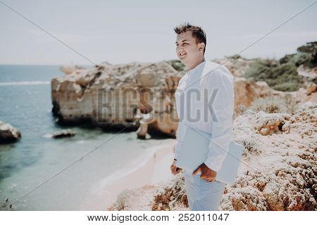 Young man holding laptop on the beach, working outdoor in summer season, digital nomad lifestyle concepts stock photo