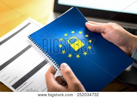 GDPR (General Data Protection Regulation) concept. Business man holding notebook with European Union (EU) flag logo and lock icon. Laptop computer and paper form on desk and table. stock photo