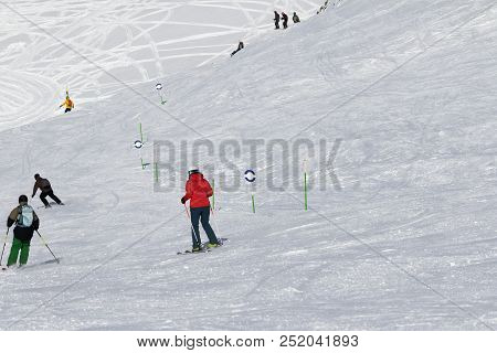 Skiers and snowboarders downhill on snowy ski trace at sun cold day. Caucasus Mountains in winter, Georgia, region Gudauri. stock photo
