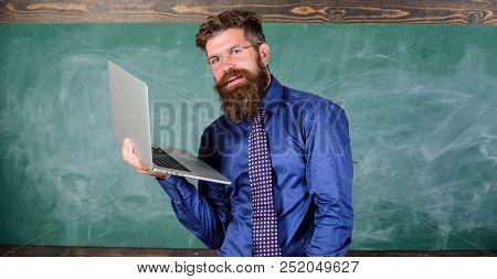 Hipster teacher wear eyeglasses and necktie holds laptop surfing internet. Distance education concept. Teacher bearded man with modern laptop surfing internet chalkboard background. Surfing internet stock photo