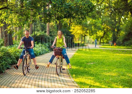Happy family.  Smiling active father and mother with kid on bicycles having fun in park. stock photo