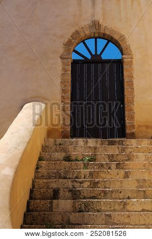 Stone stairs to the wooden gate with an arch. Arch with holes, where is visible bright blue sky. Building in former portuguese fortress in El Jadida, Morocco. stock photo