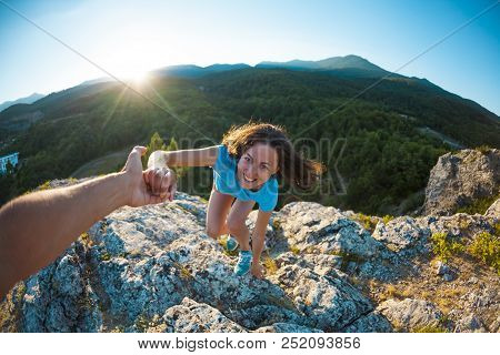 A Smiling Woman Is Climbing A Stone. Friendly Hand Of Help. A Partner Helps A Girl To Climb A Mounta