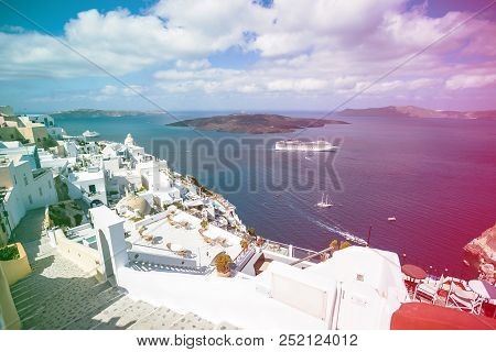 Gourgeous view from white walled town of Fira in Santorini, Greece, with ocean, cliffs and caldera of Santorini in the background. Colored light leak filter applied. stock photo