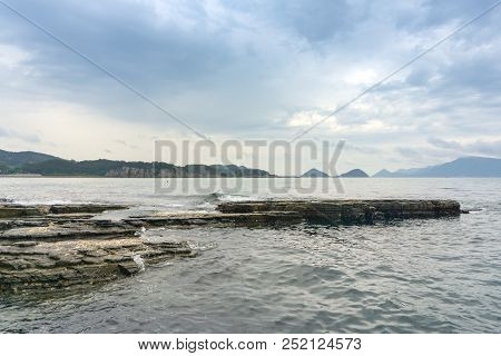 The black layers of sediment rock with shells lie slightly tilted toward the sea at Sangjogam Country Park in Geosong, South Korea stock photo