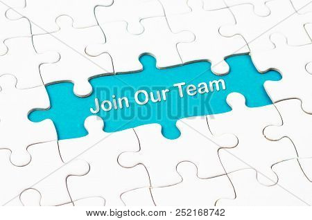 Join Our Team texts with white jigsaw puzzle board on blue background. Business concept. stock photo