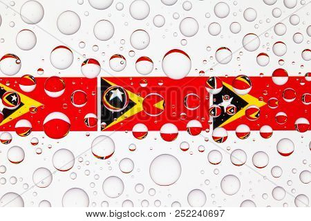 Flags  of Timor Leste behind a glass covered with raindrops. 3D illustration stock photo