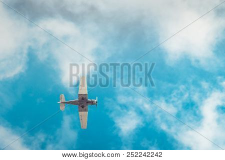 Aerobatic airplane flying high in blue sky viewed from the ground stock photo