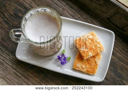 Latte coffee in a cup on wooden floor with biscuits in the morning.Breakfast on a hasty day. stock photo