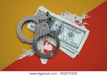Bhutan flag  with handcuffs and a bundle of dollars. Currency corruption in the country. Financial crimes stock photo