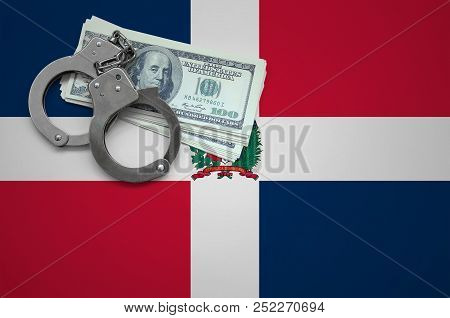 Dominican Republic flag  with handcuffs and a bundle of dollars. The concept of breaking the law and thieves crimes stock photo