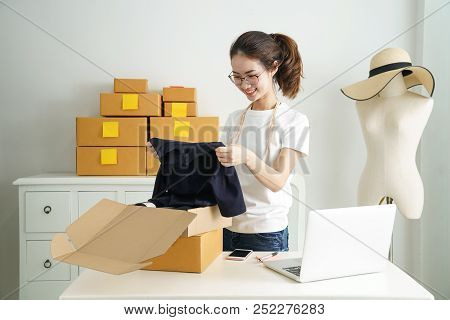 Online small business owner, Young business start up online seller owner using computer for checking the customer orders from email or website and preparing packages for product office equipment. stock photo