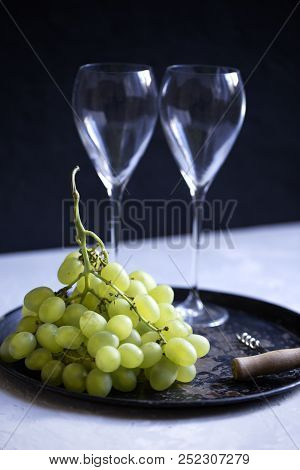 grapes, corkscrew and empty wine glasses. Picture of empty wine glass, grapes stock photo