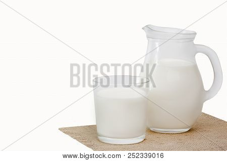 Jug of milk and glass milk on linen napkin on white background stock photo