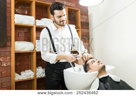 Male hairdresser rinsing client's hair with water spray in salon stock photo