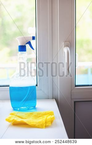 A blue window cleaner, a yellow rag on a white window sill against the window. Carrying out home inspections. Dirty and clean window, detergent, the concept of housework stock photo