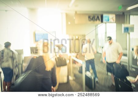 Vintage blurred passenger queuing at final gate to onboard at Dallas Fort Worth airport. Abstract people standing waiting with luggage before the jet bridge to air plane stock photo