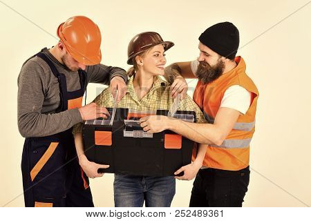 Company of cheerful workers, builder, repairer, plasterer. Man and woman with smiling faces in helmet and boilersuit, white background. Strong woman concept. Woman holds toolbox, man looking in boxes. stock photo