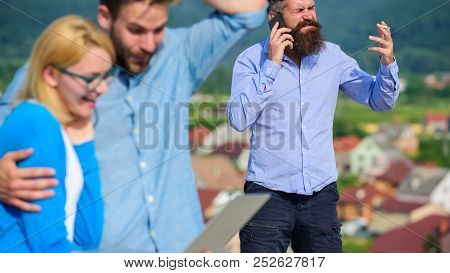 Couple colleagues flirting while boss busy with mobile conversation. Couple having fun while internet surfing outdoor. Mobile internet benefits. Colleagues use video conferencing instead mobile call stock photo